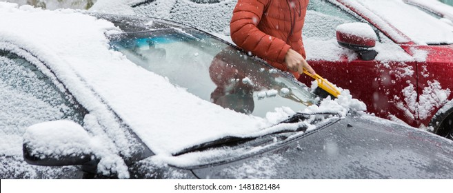 The guy cleans the car from the snow with a brush, Bad snow weather concept