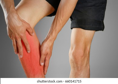 The guy clings to a bad knee. The pain in his leg. Closeup. The lesion is highlighted in red.