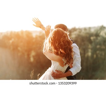the guy closes the hands of a girl in a wedding dress from the bright sun