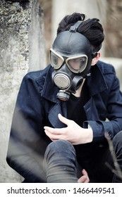 The guy in the coat and gas mask. Post-apocalyptic portrait Asian masked from radiation. The boy is Korean in a mask from poisoning with gases.