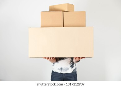 Guy, courier with bunch of cardboard boxes on neutral background. Concept delivery, moving to new apartment. Copy space.
