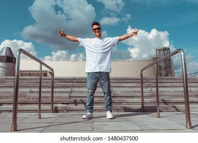 guy dancer in a white t-shirt torn jeans, stands in the summer in the city, happy smiles in sunglasses, white sneakers background building clouds