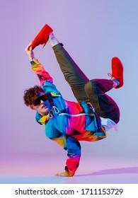 Guy dancing contemporary dance in studio. Neon light grey background. Acrobatic bboy dancer. Break dance lessons.
