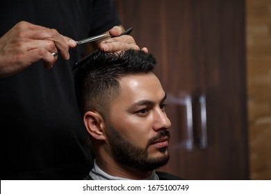 the guy is a dark-haired Asian Indian appearance on a haircut in a barbershop . cinematic image