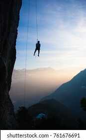 Guy descending a climbing route during sunset in the swiss alps