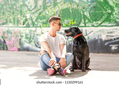 guy with a dog labrador on the street playing