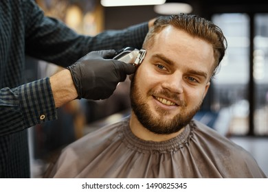 a guy doing a haircut and styling a beard in a barbershop