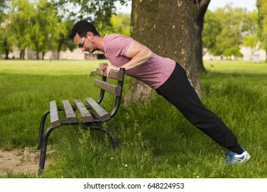 Guy doing push ups on park bench