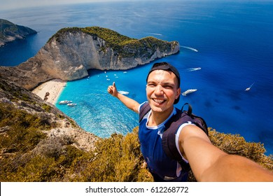 A guy doing selfie on a background of a shipwreck. Novagio beach.