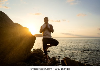 guy doing yoga poses on sharp rocks near the beach in Thailand