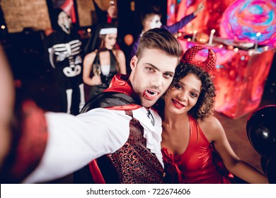 A guy dressed as a vampire and a girl dressed as a sexy demon posing and making selfie. Against the backdrop of their friends in the costumes of movie villains. Their friends are having fun