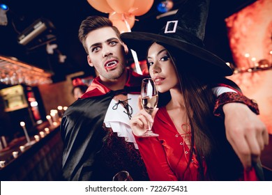 A guy dressed as a vampire and a girl dressed as a sexy witch posing with champagne glasses in their hands. Against the backdrop of their friends in the costumes of movie villains