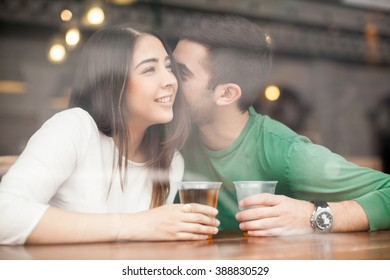 Guy drinking beer at a bar and whispering something in a woman's ear