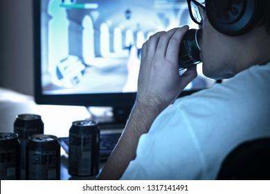 Guy drinking soda and playing video game or watching online live stream. Too much energy drink. Many empty cans of cola. Addicted gamer and computer. Sugar addiction. Geek and nerd with glasses.