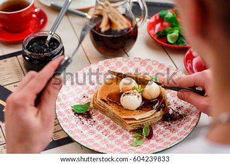 8da87a4cbac The guy is eating pancakes with maple syrup and butter. breakfast