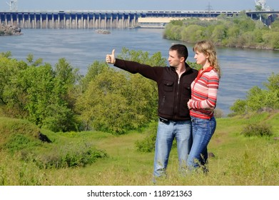 The guy embraces the girl, looks in a distance and shows a thumb. Zaporozhye. Ukraine