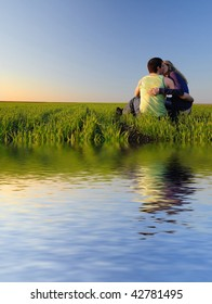 guy embraces girl on a spring field and kissing. Near the water