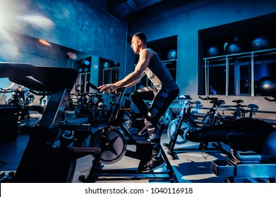 The guy is engaged in a bicycle simulator in the gym. Toned image. The guy is exercising on a stationary bike