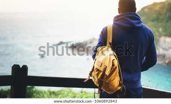 guy enjoying ocean horizon, panoramic sunrise, traveler relax holiday concept, sunlight view in trip vacation, hipster hiker tourist with backpack looking on seascape sunset, background on mountain