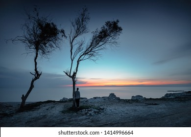 Guy enjoying sunset, back side view on a sad man looking away to the sea, solitude or freedom concept