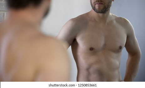 Guy examining his reflection in mirror, thinking about old age and men's health