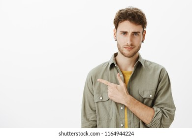 Guy expressing disbelief, unwilling to go there. Portrait of unsure good-looking male model with bristle in casual clothes, pointing left with forefinger and frowning, expressing disbelief and dislike
