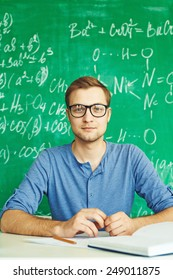 Guy in eyeglasses looking at camera at workplace