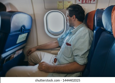 The guy is flying in an airplane. A young man is sitting in the seat of the plane during the flight.