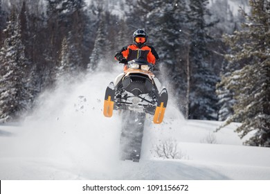 the guy is flying and jumping on a snowmobile on a background of winter forest  leaving a trail of splashes of white snow. bright snowmobile and suit without brands. extra high quality