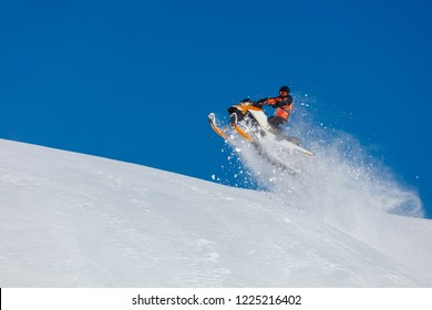 the guy is flying and jumping on a snowmobile on a background of blue sky leaving a trail of splashes of white snow. bright snowmobile and suit without brands. extra high quality