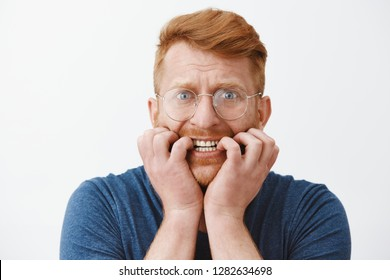 Guy freaking out, feeling worried and scared someone know his secret, biting fingernails and frowning staring intense at camera, having terrible thoughts in mind, overreacting and panicking