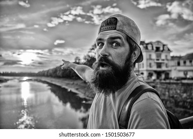 Guy in front of blue sky at evening time admire landscape. Enjoy pleasant moment. Man in cap enjoy sunset while stand on bridge. Take moment to admire sunset nature beauty. River sun reflection.