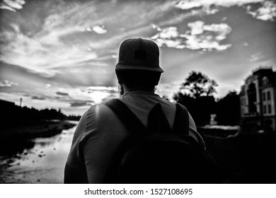 Guy in front of blue sky at evening time admire landscape. Enjoy pleasant moment. Take moment to admire sunset nature beauty. Peace and relax. Man in cap enjoy sunset while stand on bridge.