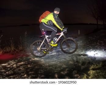 Guy fun Biker auf dem Rad während einer Nacht Reituhr in die Kamera. Der schneebedeckte Park und der leichte Nebel.