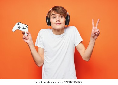 Guy Gamer in headphones with a controller in hand from the video game gaming console Orange background