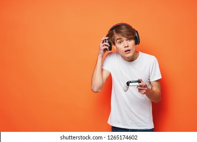 Guy Gamer in headphones with a joystick on an orange background
