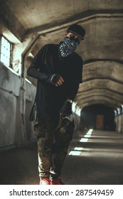 Guy in gangster clothing and face mask in catacombs