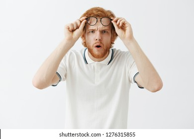 Guy getting closer look at confusing thing. Intense doubtful and questioned redhead intrigued guy with beard taking off glasses holding them on forehead folding lips and opening mouth from interest