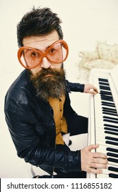Guy in giant red sunglasses while playing piano. Comic performer concept. Man in leather jacket sits near piano musical instrument in white interior on background. Man, rock musician, pianist playing.