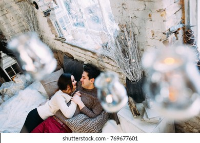 A guy with a girl is celebrating Christmas. A loving couple enjoys each other on New Year's Eve in a cozy home environment. New Year's love story.