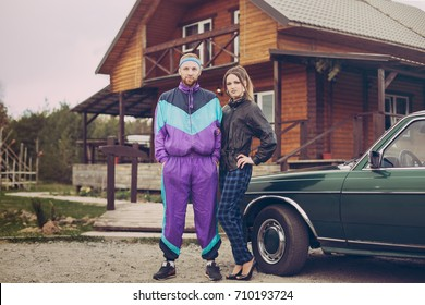 Guy and girl in clothes of the nineties, next to the old car