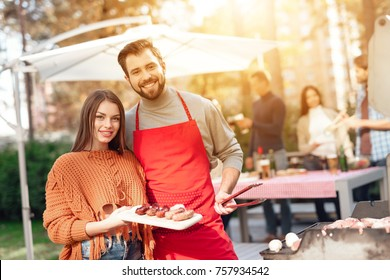 A guy and a girl are cooking barbecue food during a picnic with friends. They have fun, cook food, drink alcohol. They gathered in nature on a sunny day.