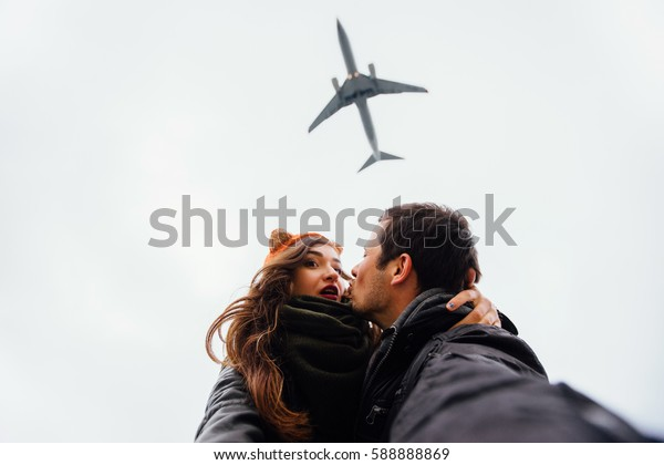 A guy and a girl, the couple embraced doing selfie standing in a picturesque place rocks. Against the background of a plane flies overhead. Autumn sky. Brunette long hair, knitted bandage