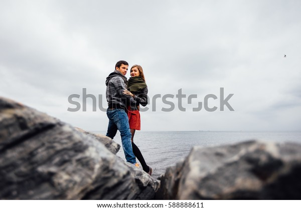 Guy and a girl, the couple posing in a picturesque place rocks, sea, autumn sky. Beautiful landscape