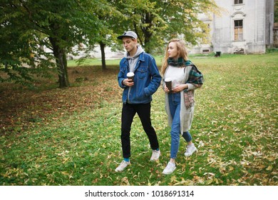 The guy with the girl drinking coffee. An old beautiful house. Beautiful young couple. The guy is a hipster. Stylish girl in a coat