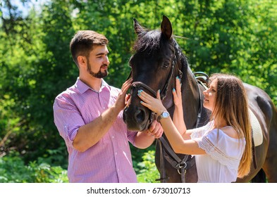 the guy with the girl goes on the ranch and play the fool. around sports horses and horses. the guy in jeans, a hat and a shirt a cage.