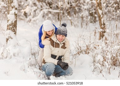 The guy and the girl have a rest in the winter woods. Husband and wife in the snow. Young couple walking in winter park