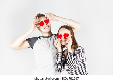 guy and girl hold red hearts on  eyes have fun