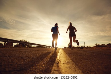 A guy and a girl jog along the road at sunset in nature.
