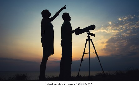 The guy with the girl looking at the sky through a telescope